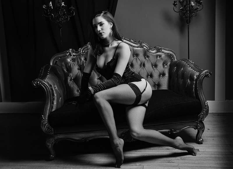 dramatic light for a vintage look on a vintage couch. Woman wearing fishnets and full corset outfit
