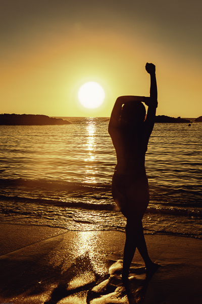 Hawaii sunset beach shoot with woman standing facing the sun