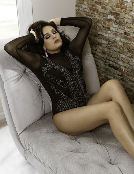 Latina woman with beautiful make up, beaded sheer black bodysuit
