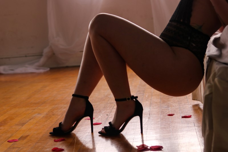 heels and legs with rose petals on the floor